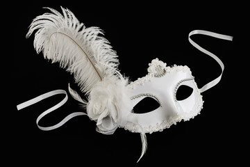 White carnival mask with feather on black background