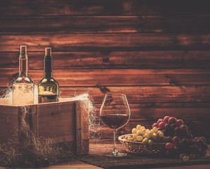 Bottles of red and white wine, glass in a wooden interior