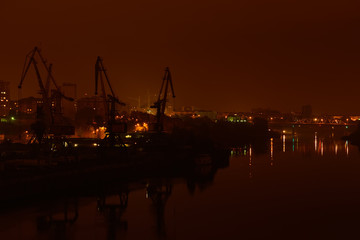Night view of river port. Bridge and buildings