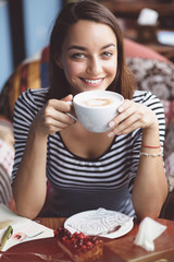 Young woman drinking coffee in urban cafe