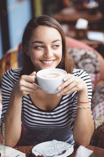 Young woman drinking coffee in urban cafe - 69832563
