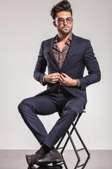 seated elegant man closing his coat