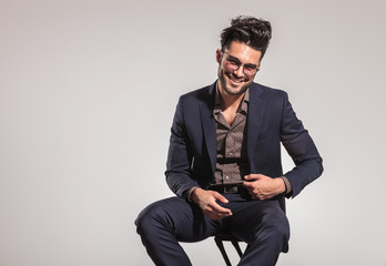 smart casual man in suit sitting on chair and laughing