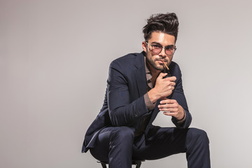 fashion man with glasses lighting his cigarette