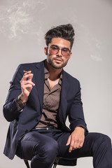portrait of an elegant young man in suit smoking