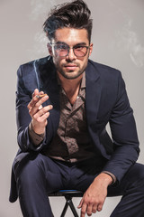 fashion man in suit and glasses smoking and sitting