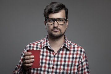 Handsome hipster modern man and cup of coffee in hand.
