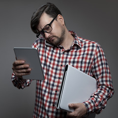 Handsome hipster busy man with many gadgets in hands.