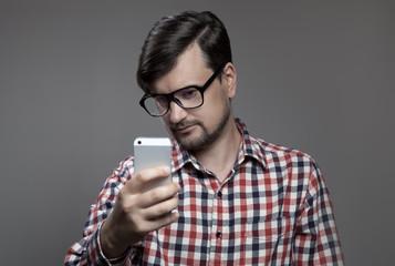 Handsome hipster modern man self shooting on smartphone camera.
