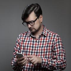 Handsome hipster modern man using smartphone.