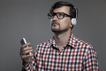 Handsome hipster modern man listen music in headphones.