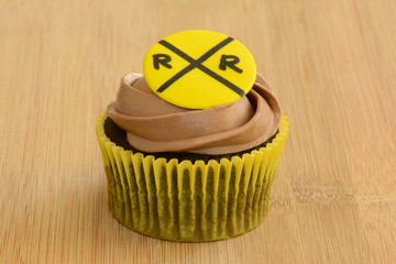 Single frosted chocolate cupcake with crossing railroad sign