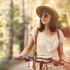 Girl on a bicycle in coniferous forest. Lightleak effect and ins