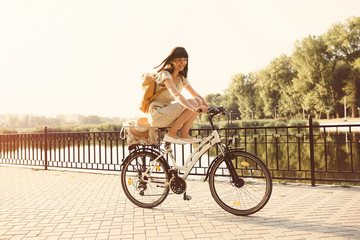 Girl riding a bicycle in park near the lake. Lightleak effect an