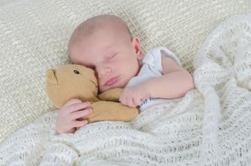 Baby hält Bärchen fest