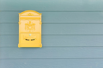 Yellow mailbox with green wood background