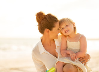 Portrait of happy mother and baby girl on the beach