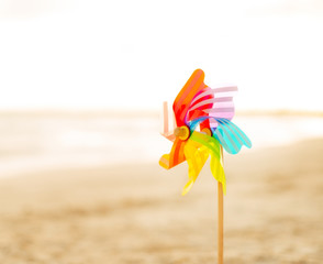 Closeup on colorful windmill toy standing on the beach