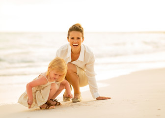 Happy mother and baby girl playing on the beach in the evening