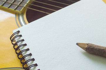 Notebook and wooden pencil on guitar,Writing music