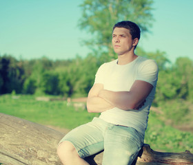 Handsome man relaxing on a nature, soft sunny sunset