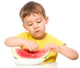 Little boy is eating watermelon