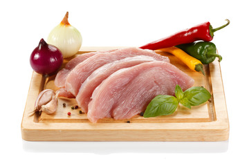 Raw turkey fillets on cutting board and vegetables