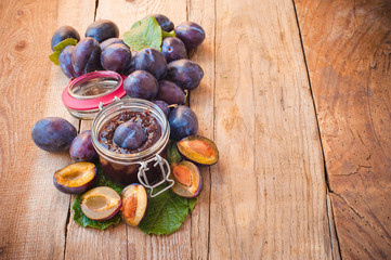 Jar of plum jam surrounded by plums on background wooden rural t