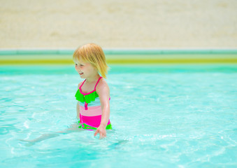 Baby girl playing in swimming pool