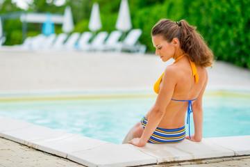 Young woman sitting near swimming pool