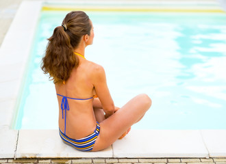 Young woman sitting near swimming pool. rear view