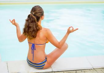 Young woman in yoga pose sitting near swimming pool