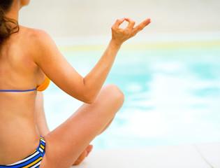 Closeup on young woman in yoga pose sitting near swimming pool