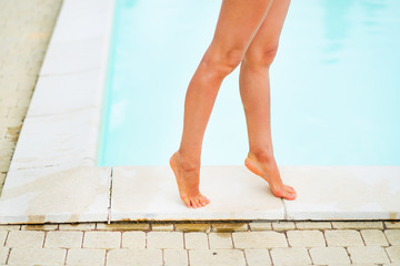 Closeup on young woman legs near swimming pool