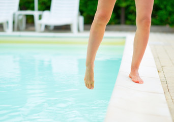 Closeup on young woman checking water in swimming pool