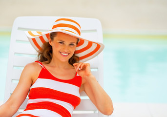 Portrait of happy young woman in hat laying on sunbed