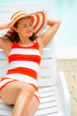 Portrait of smiling young woman in hat laying on sunbed