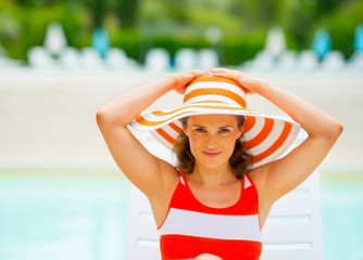 Portrait of young woman in hat sitting on sunbed