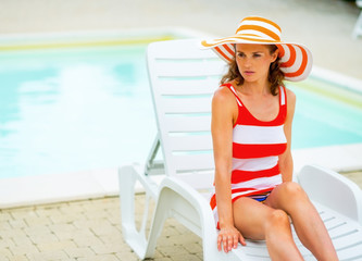 Relaxed young woman in hat sitting on sunbed