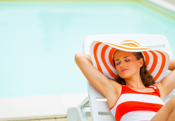 Relaxed young woman in hat laying on sunbed