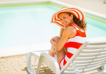 Happy young woman in hat sitting on sunbed