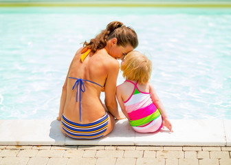 Mother and baby girl sitting near swimming pool. rear view
