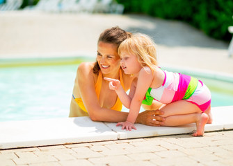 Portrait of happy mother and baby girl in swimming pool