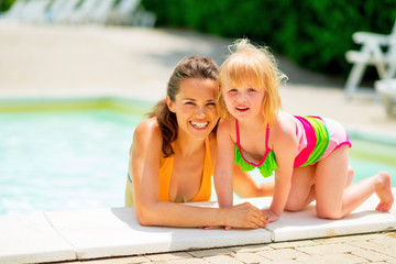 Portrait of smiling mother and baby girl at swimming pool