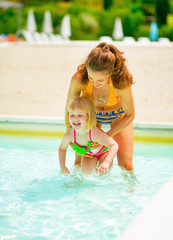 Mother and baby girl playing in swimming pool