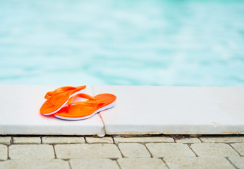 Closeup on sandals laying near swimming pool
