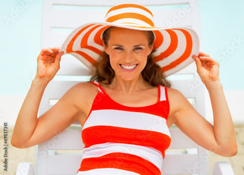 canvas print picture Portrait of smiling young woman in hat laying on chaise-longue