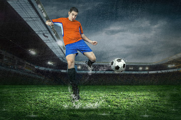 Football player with ball in action under rain in stadium