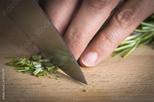 Fotobehang Koken Cocinero picando romero a cuchillo en la mesa de la cocina