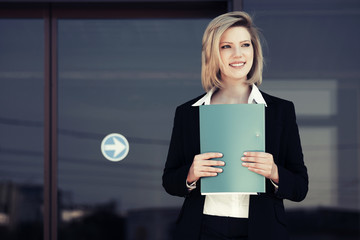 Happy young business woman with a folder at the office building